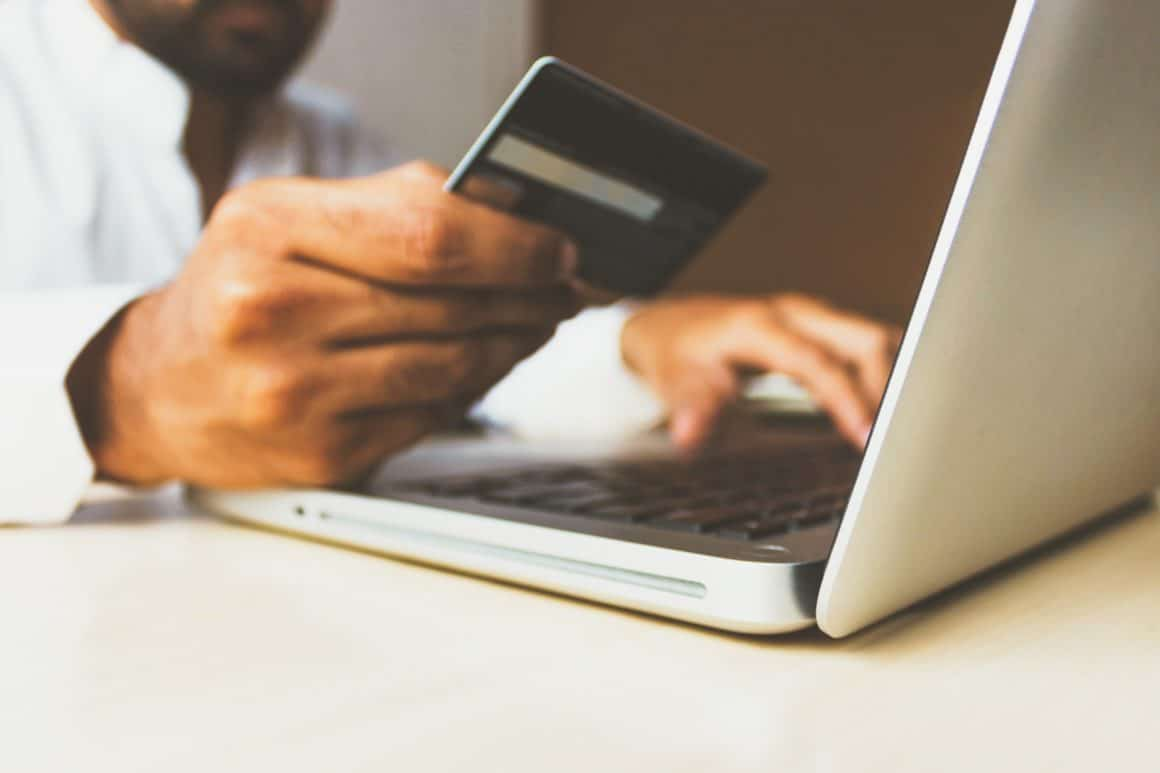 Photo of man typing on computer while holding credit card