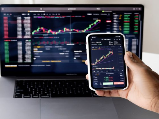 Phone and computer with line graphs tracking fixed-income investments